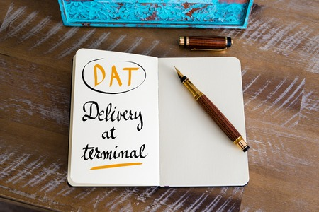dat: Retro effect and toned image of a fountain pen on a notebook. Business Acronym DAT as Delivery At Terminal as business concept image