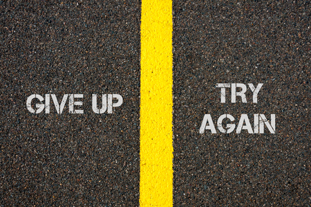 financial questions: Antonym concept of GIVE UP versus TRY AGAIN written over tarmac, road marking yellow paint separating line between words