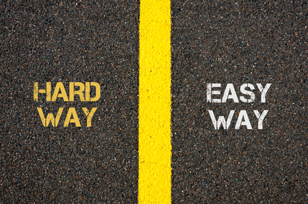 easy way: Antonym concept of HARD WAY versus EASY WAY written over tarmac, road marking yellow paint separating line between words Stock Photo