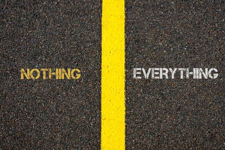 versus: Antonym concept of NOTHING versus EVERYTHING written over tarmac, road marking yellow paint separating line between words