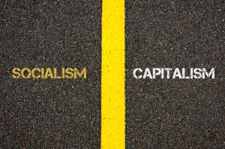 socialism: Antonym concept of SOCIALISM versus CAPITALISM written over tarmac, road marking yellow paint separating line between words Stock Photo