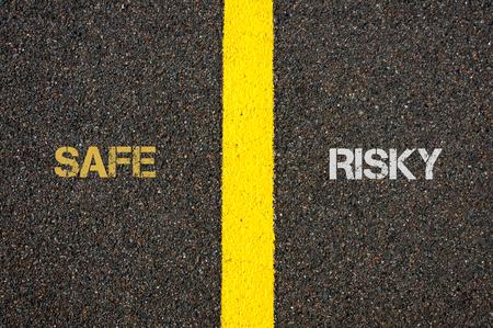 risky: Antonym concept of SAFE versus RISKY written over tarmac, road marking yellow paint separating line between words