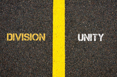 Antonym concept of DIVISION versus UNITY written over tarmac, road marking yellow paint separating line between words Stock Photo