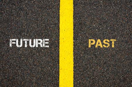 versus: Antonym concept of FUTURE versus PAST written over tarmac, road marking yellow paint separating line between words Stock Photo
