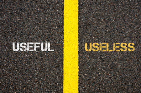 Antonym concept of USEFUL versus USELESS written over tarmac, road marking yellow paint separating line between words Stock Photo