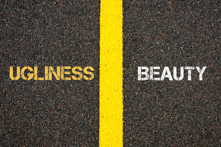 ugliness: Antonym concept of UGLINESS versus BEAUTY written over tarmac, road marking yellow paint separating line between words