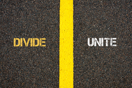 unite: Antonym concept of DIVIDE versus UNITE written over tarmac, road marking yellow paint separating line between words