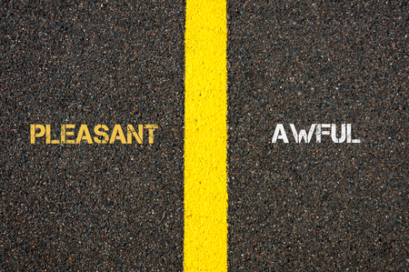 awful: Antonym concept of PLEASANT versus AWFUL written over tarmac, road marking yellow paint separating line between words