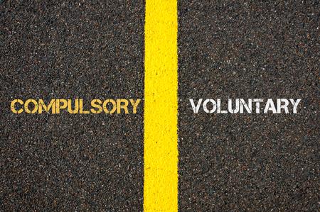compulsory: Antonym concept of COMPULSORY versus VOLUNTARY written over tarmac, road marking yellow paint separating line between words Stock Photo