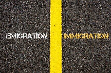 emigration immigration: Antonym concept of EMIGRATION versus IMMIGRATION written over tarmac, road marking yellow paint separating line between words Stock Photo