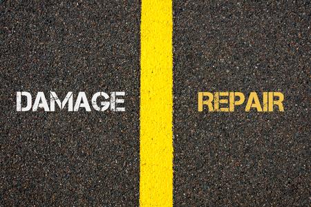 contradiction: Antonym concept of DAMAGE versus REPAIR written over tarmac, road marking yellow paint separating line between words