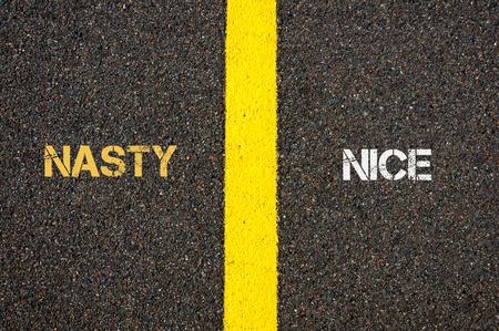 nasty: Antonym concept of NASTY versus NICE written over tarmac, road marking yellow paint separating line between words