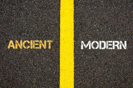 versus: Antonym concept of ANCIENT versus MODERN written over tarmac, road marking yellow paint separating line between words