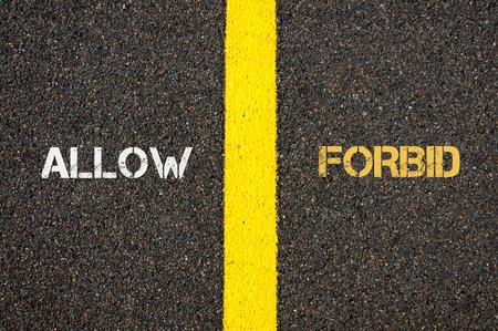 contradiction: Antonym concept of ALLOW versus FORBID written over tarmac, road marking yellow paint separating line between words