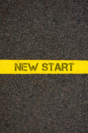 challenges ahead: Road marking yellow paint dividing line with words NEW START, concept image