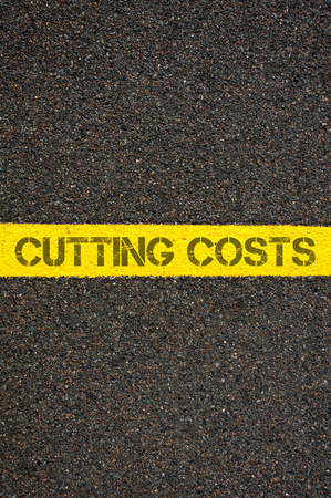 cutting costs: Road marking yellow paint dividing line with words CUTTING COSTS, concept image Stock Photo