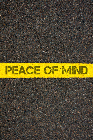 contradiction: Road marking yellow paint dividing line with words PEACE OF MIND, concept image