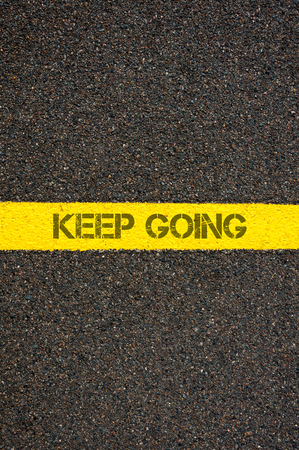 contradiction: Road marking yellow paint dividing line with words KEEP GOING, concept image