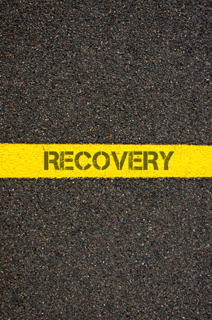 road to recovery: Road marking yellow paint dividing line with word RECOVERY, concept image Stock Photo