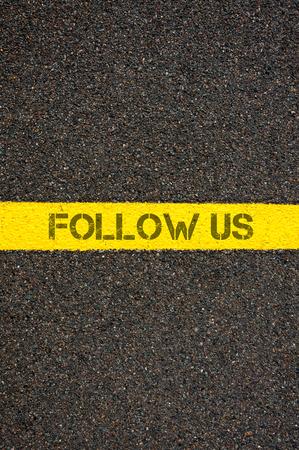 road marking: Road marking yellow paint dividing line with words FOLLOW US, concept image