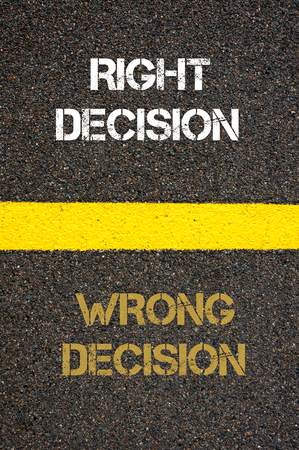 contradiction: Antonym decision concept of WRONG DECISION versus RIGHT DECISION written over tarmac, road marking yellow paint separating line between words