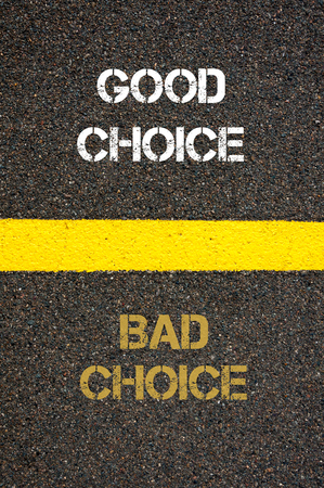 versus: Antonym decision concept of BAD CHOICE versus GOOD CHOICE written over tarmac, road marking yellow paint separating line between words