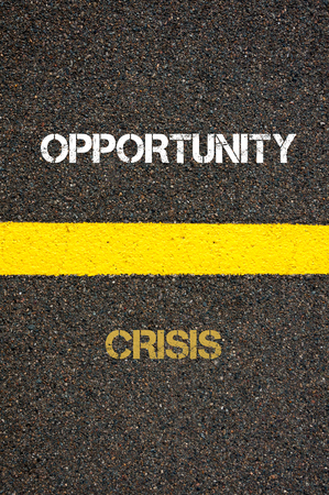 financial questions: Antonym decision concept of CRISIS versus OPPORTUNITY written over tarmac, road marking yellow paint separating line between words