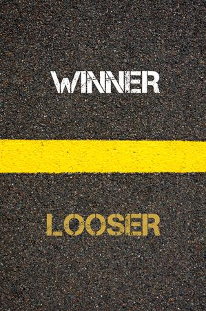 looser: Antonym decision concept of LOOSER versus LOOSER written over tarmac, road marking yellow paint separating line between words