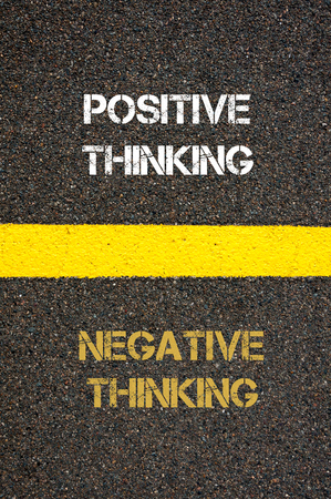 negative thinking: Antonym decision concept of NEGATIVE THINKING versus POSITIVE THINKING written over tarmac, road marking yellow paint separating line between words Stock Photo