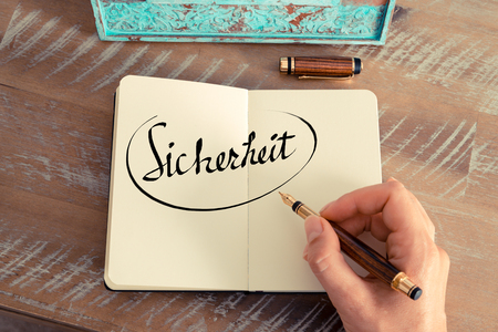 sicherheit: Retro effect and toned image of woman hand writing a note on a notebook. Handwritten text in German Sicherheit   - translation : Safety as business concept image