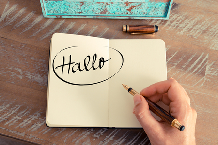 hallo: Retro effect and toned image of woman hand writing a note on a notebook. Handwritten text in German Hallo  - translation : Hello as business concept image