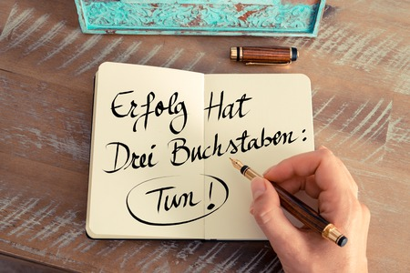 buchstaben: Retro effect and toned image of woman hand writing a note on a notebook. Handwritten text in German  Erfolg Hat Drei Buchstaben: Tun! - translation : Success Has Three Letters: Do, concept image