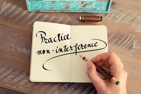 interference: Retro effect and toned image of a woman hand writing a note with a fountain pen on a notebook. Handwritten text Practice Non Interference as success and evolution concept image Stock Photo