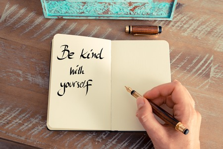 Retro effect and toned image of a woman hand writing a note with a fountain pen on a notebook. Handwritten text Be Kind With Yourself as success and evolution concept image