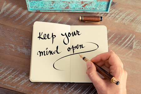 keep your hands: Retro effect and toned image of a woman hand writing a note with a fountain pen on a notebook. Handwritten text Keep Your Mind Open as success and evolution concept image
