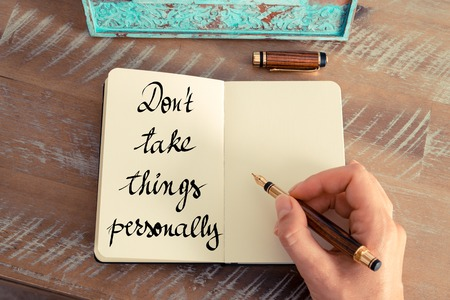 personally: Retro effect and toned image of a woman hand writing a note with a fountain pen on a notebook. Handwritten text Dont Take Things Personally as success and evolution concept image