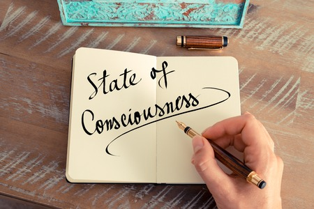consciousness: Retro effect and toned image of a woman hand writing a note with a fountain pen on a notebook. Handwritten text State Of Consciousness as success and evolution concept image Stock Photo