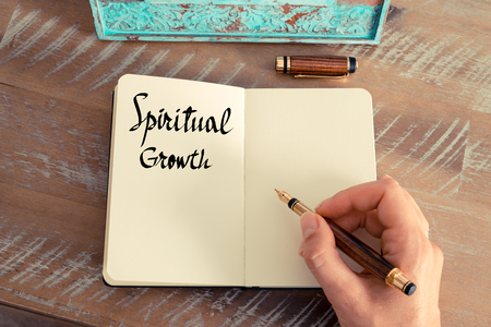 spiritual growth: Retro effect and toned image of a woman hand writing a note with a fountain pen on a notebook. Handwritten text Spiritual Growth as success and evolution concept image