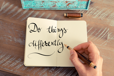 differently: Retro effect and toned image of a woman hand writing a note with a fountain pen on a notebook. Handwritten text Do Things Differently as success and evolution concept image Stock Photo