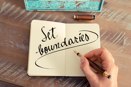 Retro effect and toned image of a woman hand writing a note with a fountain pen on a notebook. Handwritten text Set Boundaries as success and evolution concept image Stock Photo