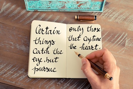 pursue: Retro effect and toned image of a woman hand writing on a notebook. Handwritten quote Certain things catch your eye, but pursue only those that capture the heart as inspirational concept image