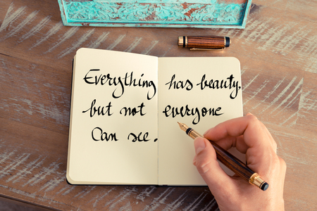 but think: Retro effect and toned image of a woman hand writing on a notebook. Handwritten quote Everything has beauty, but not everyone can see as inspirational concept image Stock Photo