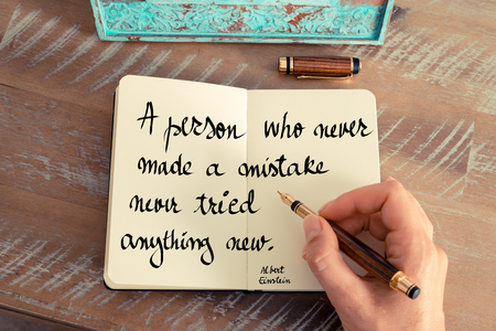 person writing: Retro effect and toned image of a woman hand writing on a notebook. Handwritten quote A person who never made a mistake never tried anything new  - Albert Einstein as inspirational concept image