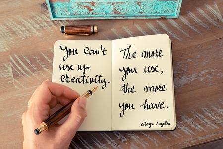 Retro effect en gestemd beeld van een vrouwenhand die op een notitieboekje schrijven. Handgeschreven citaat Je kunt creativiteit niet opgebruiken. Hoe meer je gebruikt, hoe meer je hebt - Maya Angelou als een inspirerend concept