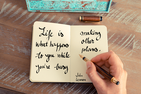happens: Retro effect and toned image of a woman hand writing on a notebook. Handwritten quote Life is what happens to you while youre busy making other plans. - John Lennon as inspirational concept image Stock Photo
