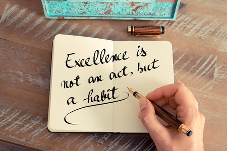 but think: Retro effect and toned image of a woman hand writing on a notebook. Handwritten quote Excellence is not an act, but a habit as inspirational concept image