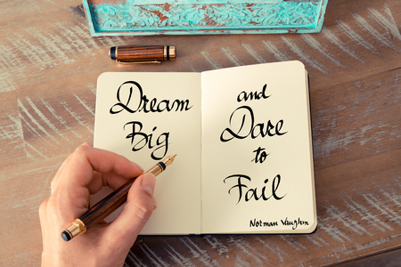 dare: Retro effect and toned image of a woman hand writing on a notebook. Handwritten quote Dream big and dare to fail - Norman Vaughan as inspirational concept image