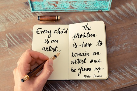 pablo picasso: Retro effect and toned image of a woman hand writing on a notebook. Handwritten quote Every child is an artist.  The problem is how to remain an artist once he grows up - Pablo Picasso