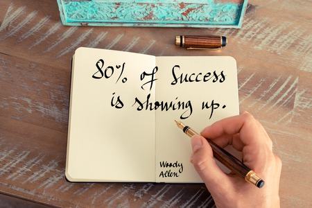 Retro effect and toned image of a woman hand writing on a notebook. Handwritten quote Eighty percent of success is showing up  - Woody Allen as inspirational concept image Stock Photo