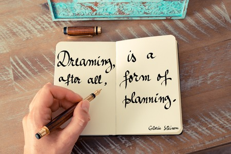 gloria: Retro effect and toned image of a woman hand writing on a notebook. Handwritten quote Dreaming, after all, is a form of planning - Gloria Steinem as inspirational concept image Stock Photo